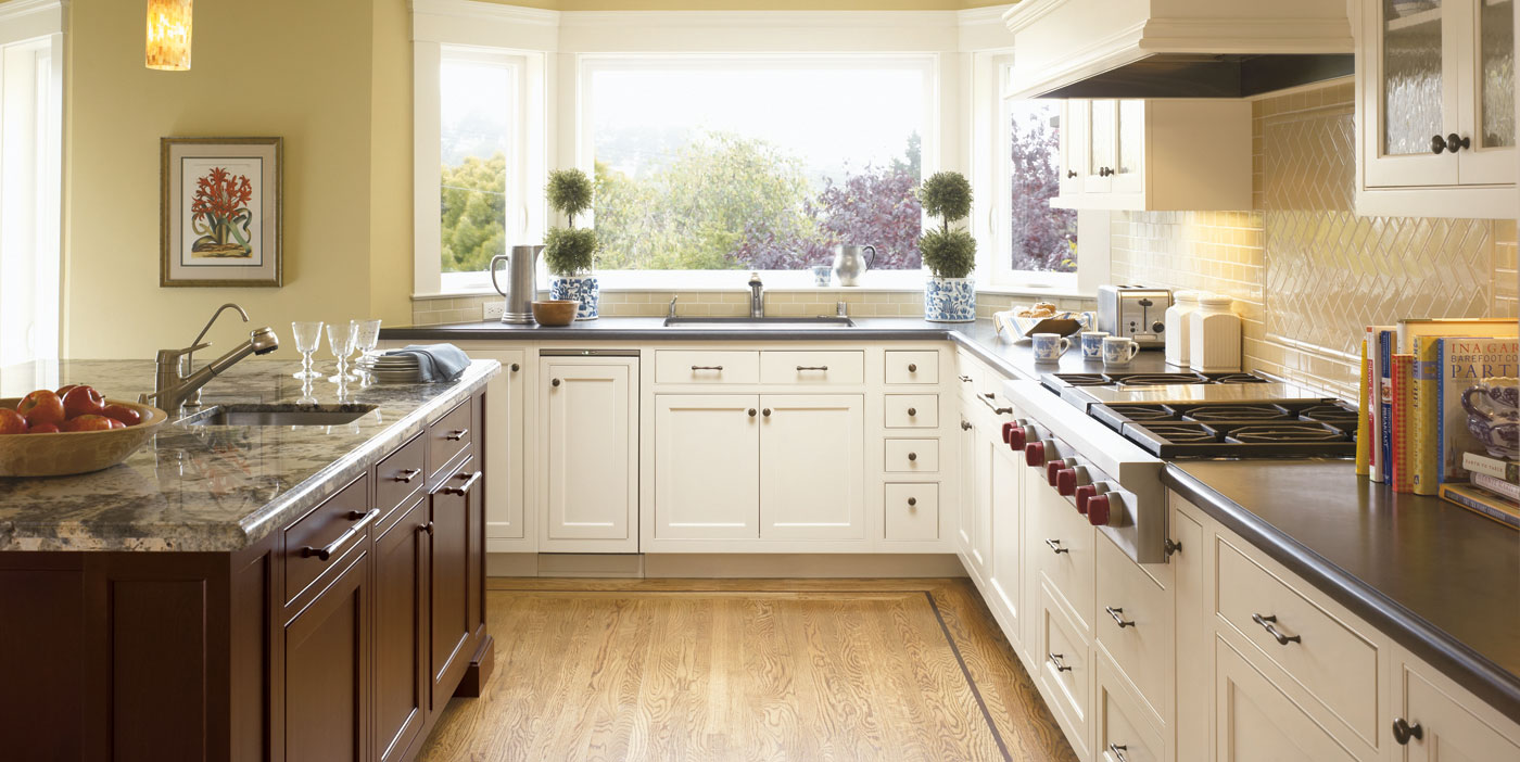 white aristokraft cabinets with black countertop and oven with wooden floor for kitchen decor ideas