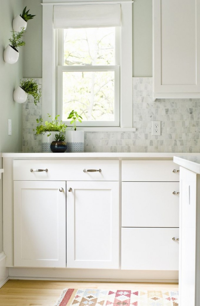 White Aristokraft Cabinets With Silver Handle And White Countertop Under The White Single Hung Window For Kitchen Decor Ideas