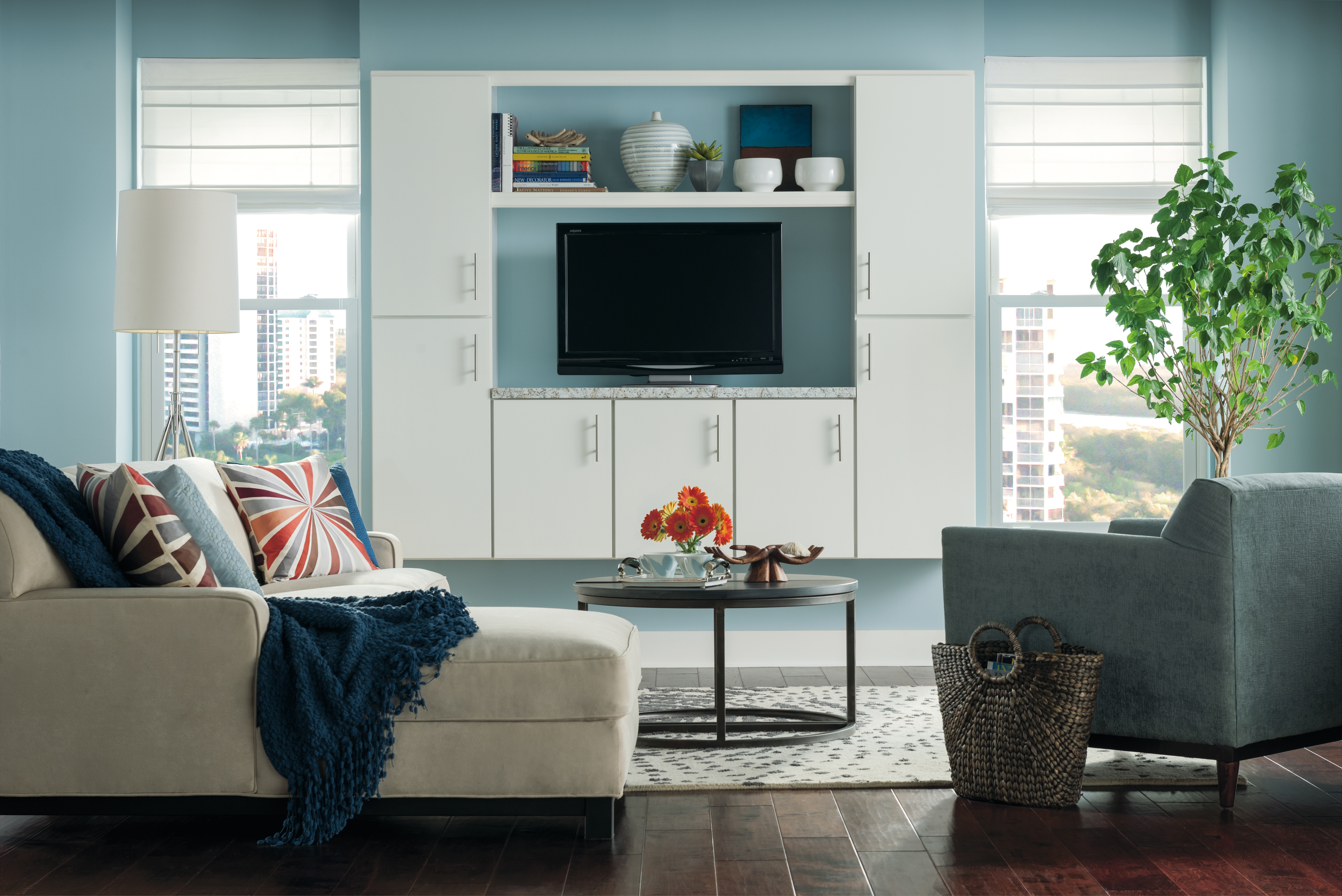 white aristokraft cabinets with tv stand on blue wall plus white sofa on brown ceramics floor for family room decor ideas