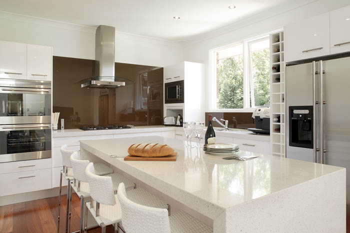 white caesarstone Countertops with chairs plus oven and fridge for kitchen decor ideas