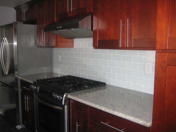 White Cancos Tile Back Splash With White Countertop Plus Natural Brown Wood Kitchen Cabinet Plus Oven For Kitchen Decor Ideas