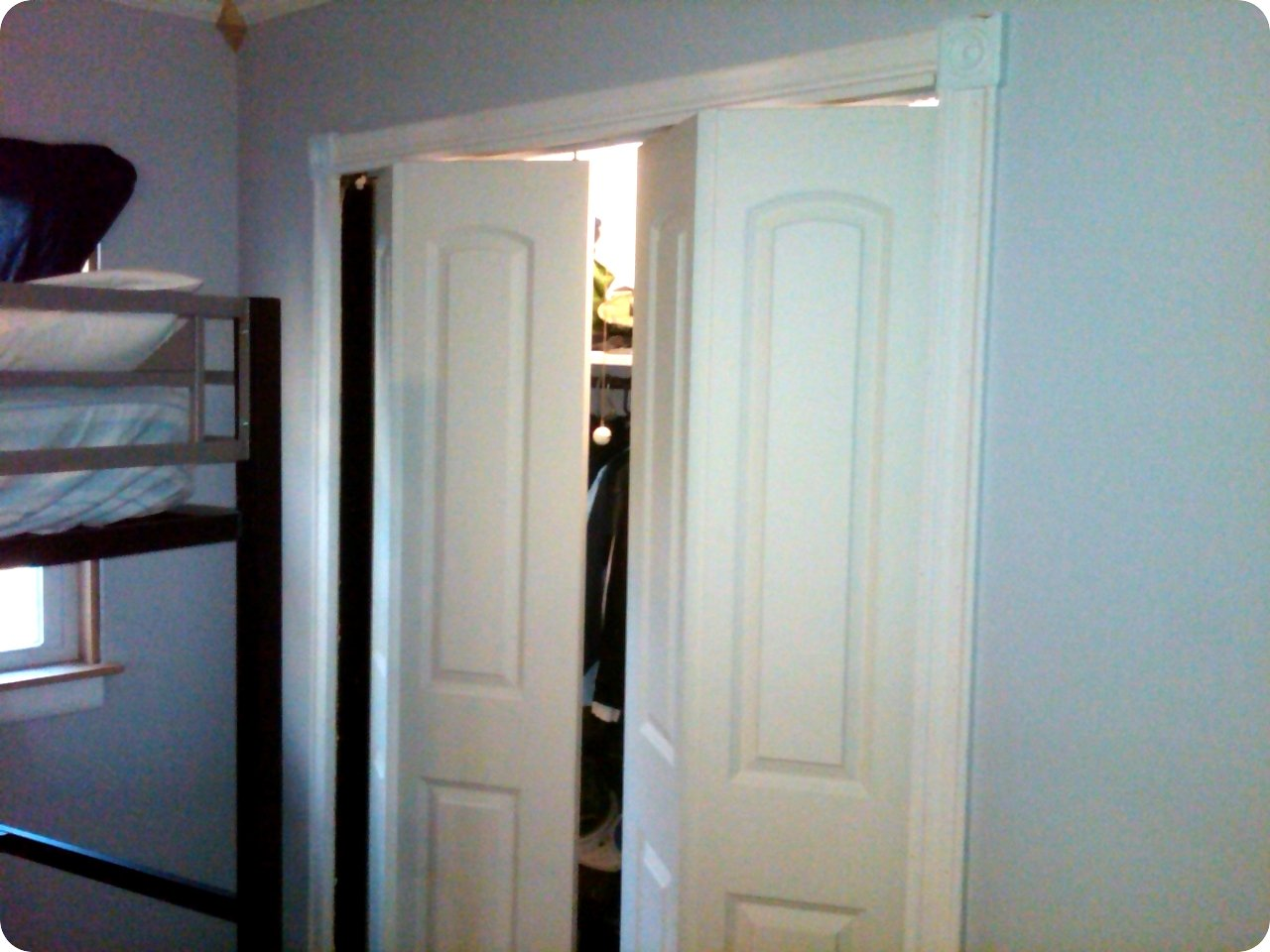 White Folding Closet Doors On Blue Wall With Loft Bed