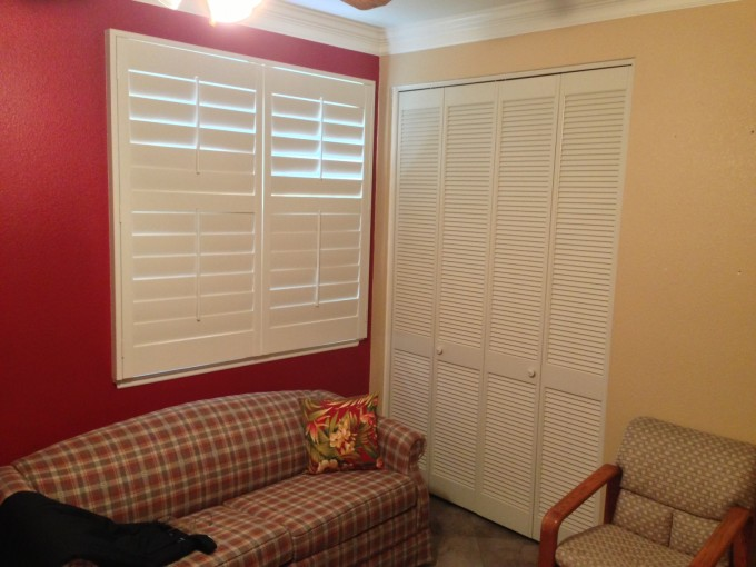 White Folding Closet Doors On Peachpuff Wall With Checked Sofa Plus Floral Cushions