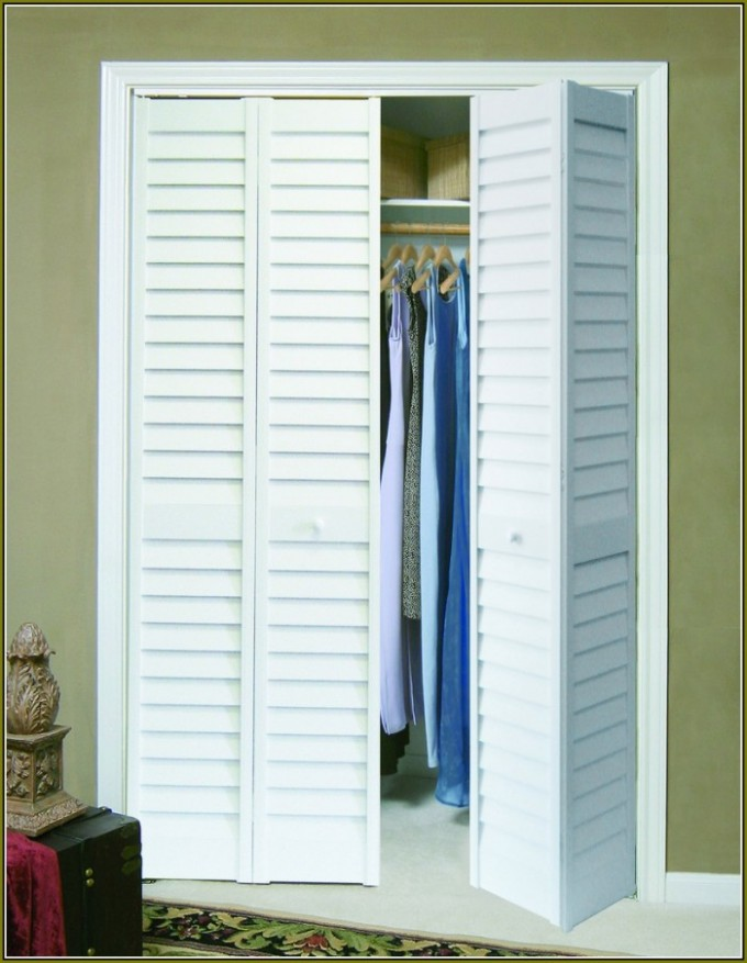 White Folding Closet Doors Wfilled With Clothes On Grey Wall