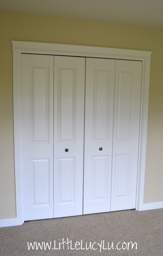 White Folding Closet Doors With Silver Round Handle On Cream Wall