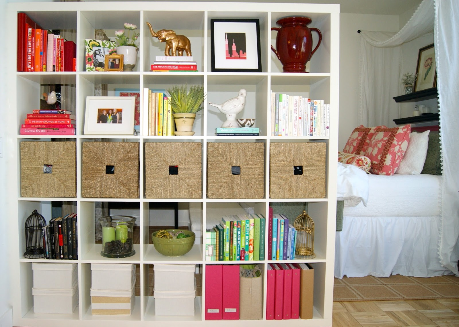 white IKEA Expedit bookcase filled with books and frame plus many other things with cream floor and white bedding