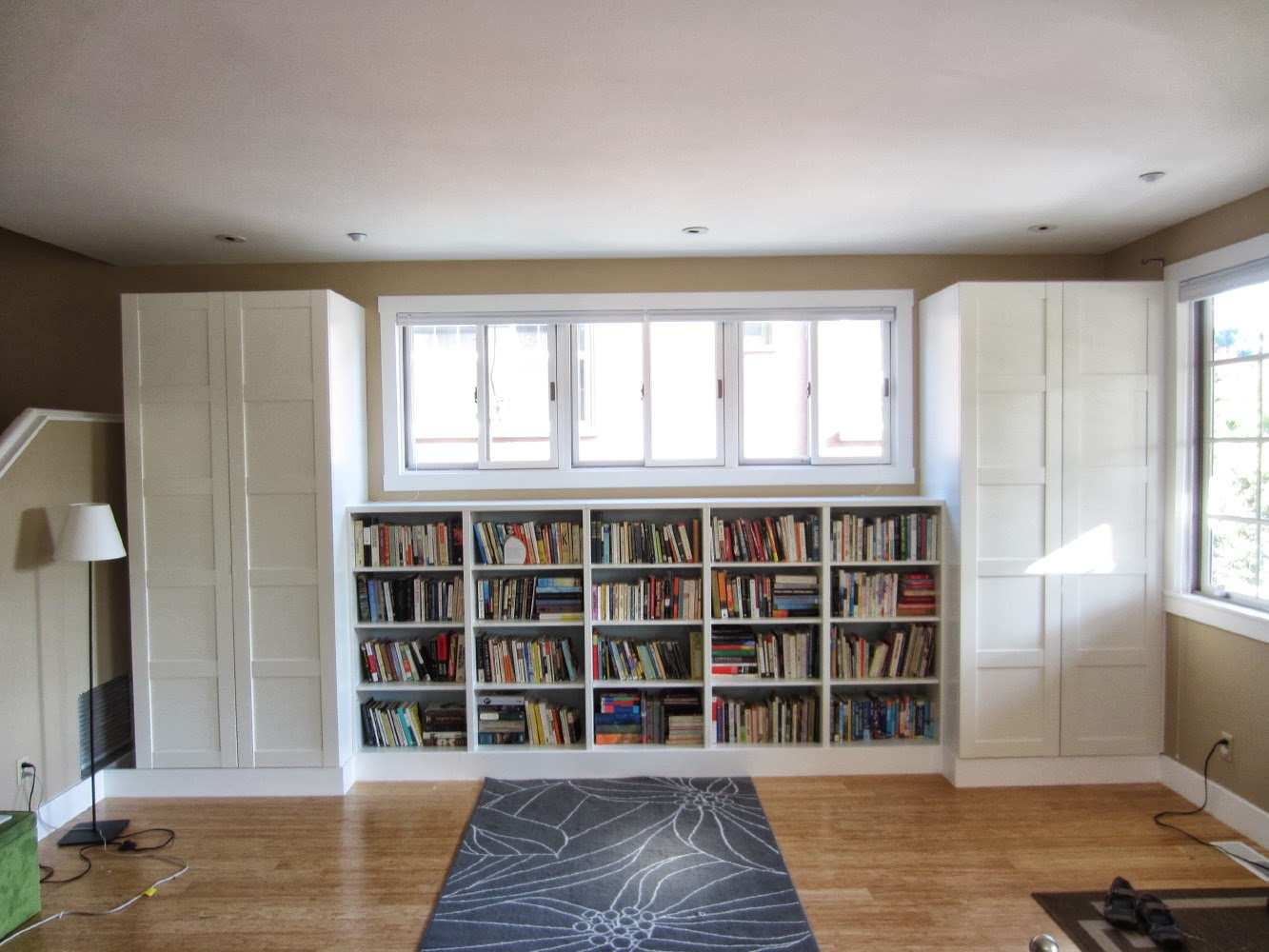 white ikea expedit bookcase filled with books on tan room with double white cupboard and slider window