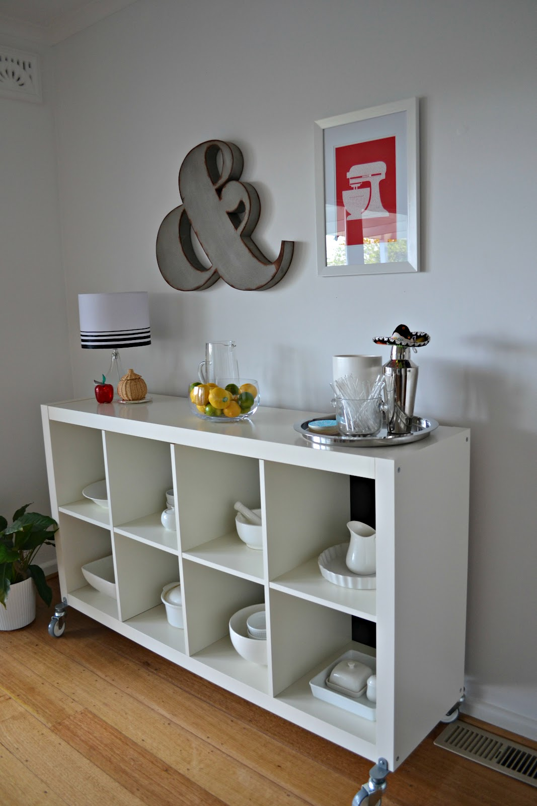 white ikea expedit bookcase with kitchen furniture plus a table standing lamp and white wall plus wooden floor
