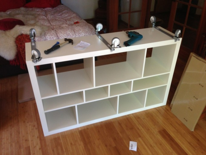 White Ikea Expedit Bookcase With Wheels On Wooden Floor Near Bedding