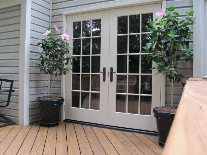 White Reliabilt Doors With Black Handle Matched With Brown Decking And White Wall