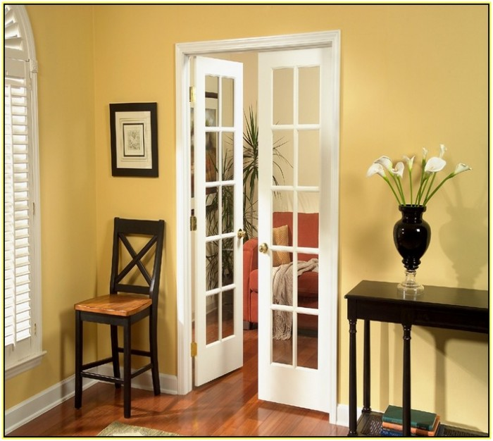 white reliabilt doors with golden handle matched with yellow wall and wooden floor