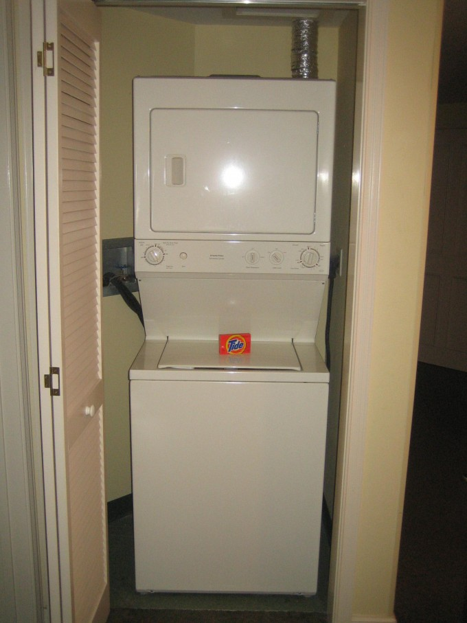 White Stackable Washer And Dryer On Laundry Space With Wheat Door Ideas