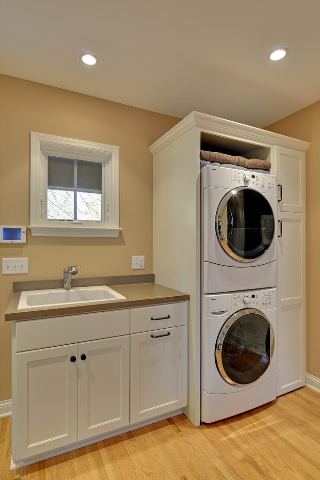 White Stackable Washer And Dryer With White Cabinet Plus White Sink On Laundry Room With Wooden Flooring