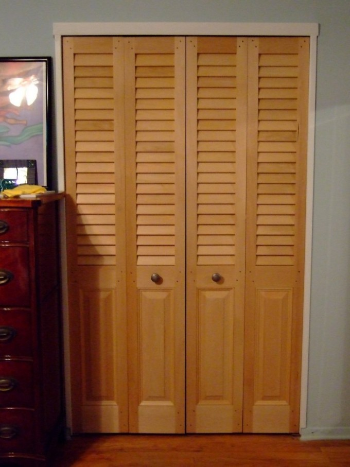 Wooden Folding Closet Doors On Grey Wall With Dresser And Picture Above