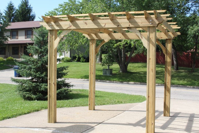 Wooden Pergola Plans With Four Props On Backyard With Green Grass