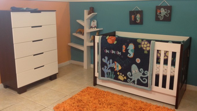 Baby Nursery Room Decoration With White Crib By Babyletto On White Ceramics Floor Plus Orange Carpet Matched With Orange And Blue Wall Plus White Baseboard Molding Plus White Cabinet