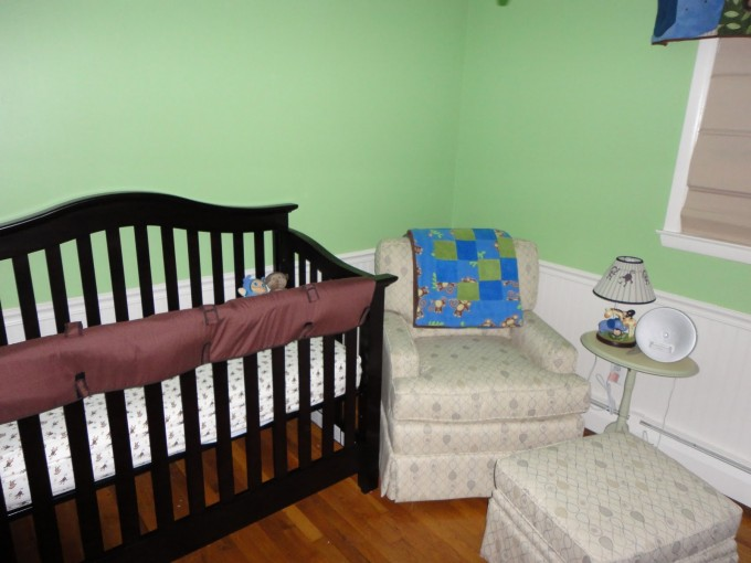 Black Wooden Munire Crib On Wooden Floor Matched With Green Wall With White Wainscoting Plus Small Sofa With Matching Ottoman For Small Nursery Decor Ideas