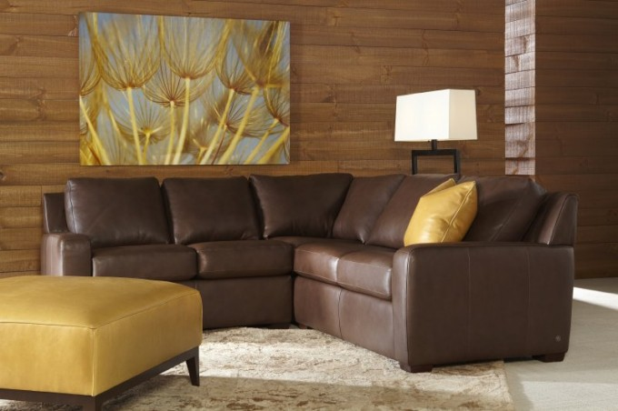 Brown Leather Sectional Sleeper Sofa On Wheat Carpet Matched With Brown Wooden Wall Plus Ottoman For Living Room Decor Ideas