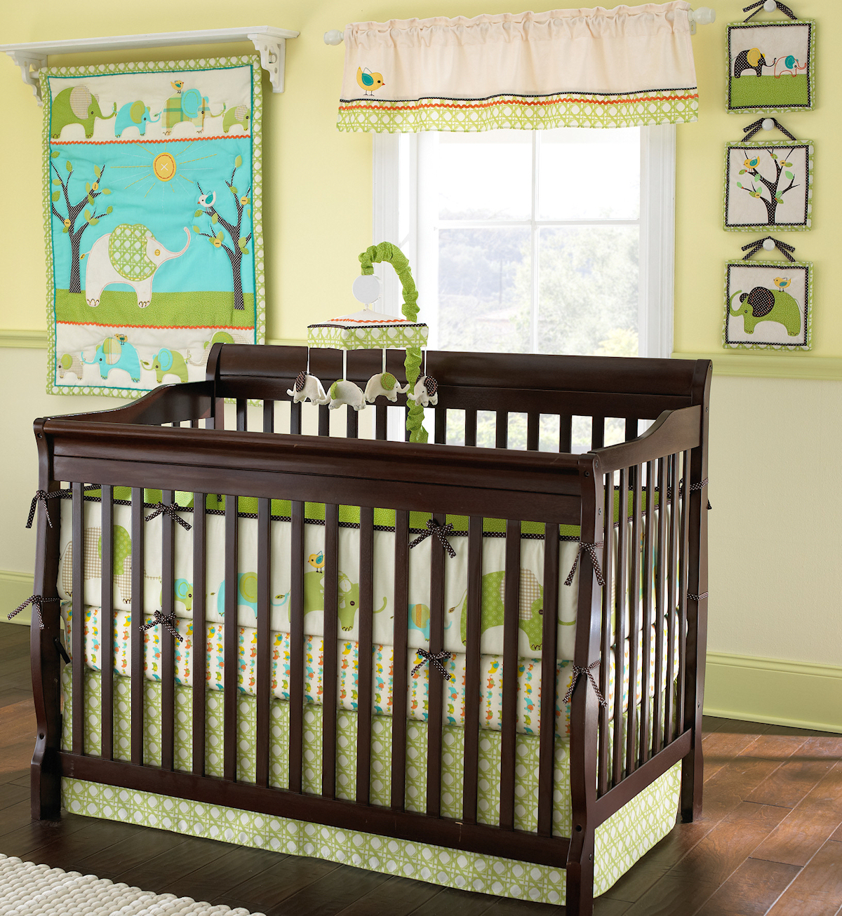 brown wooden crib with green laura ashley bedding on wooden floor for nursery decor ideas