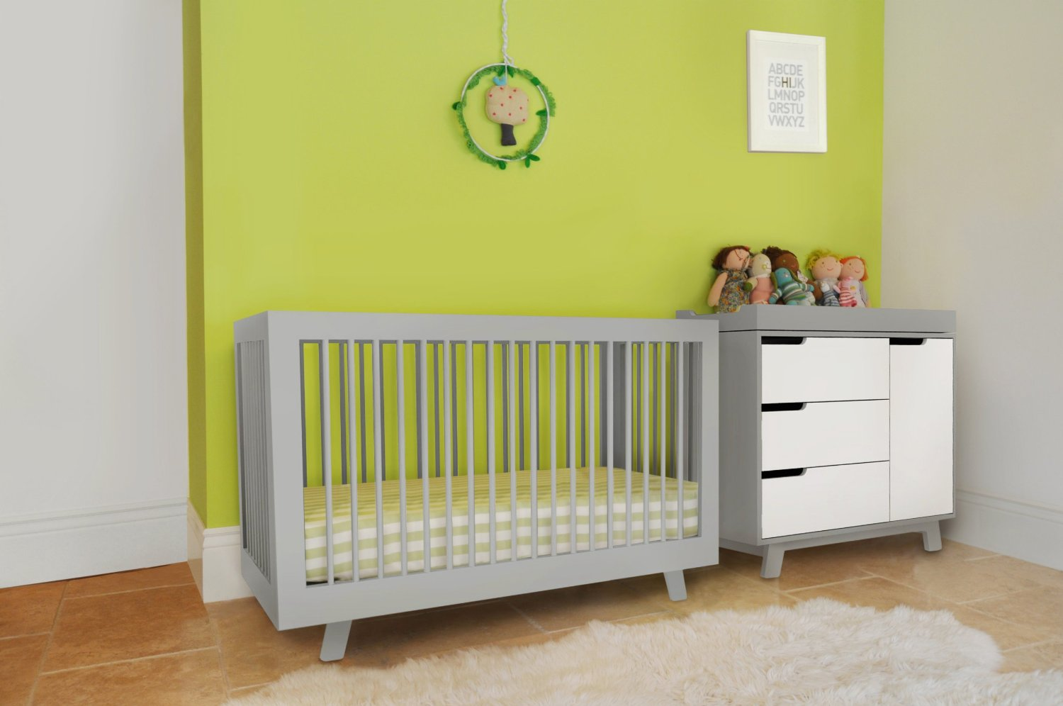 charming nursery decoration with grey crib with white bedding by babyletto on sandy brown ceramics floor matched with yellow wall plus white baseboard molding plus cabinets