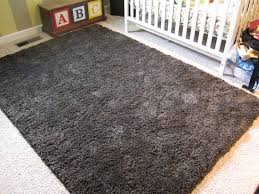 charming rectangle shag rugs in dark grey on white floor plus white crib for nursery decor ideas