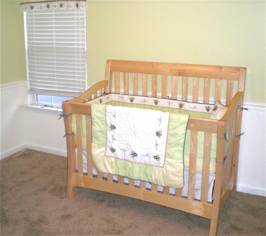 cream wooden munire crib before the yellow wall with white wainscoting plus window with blinds for nursery decor ideas