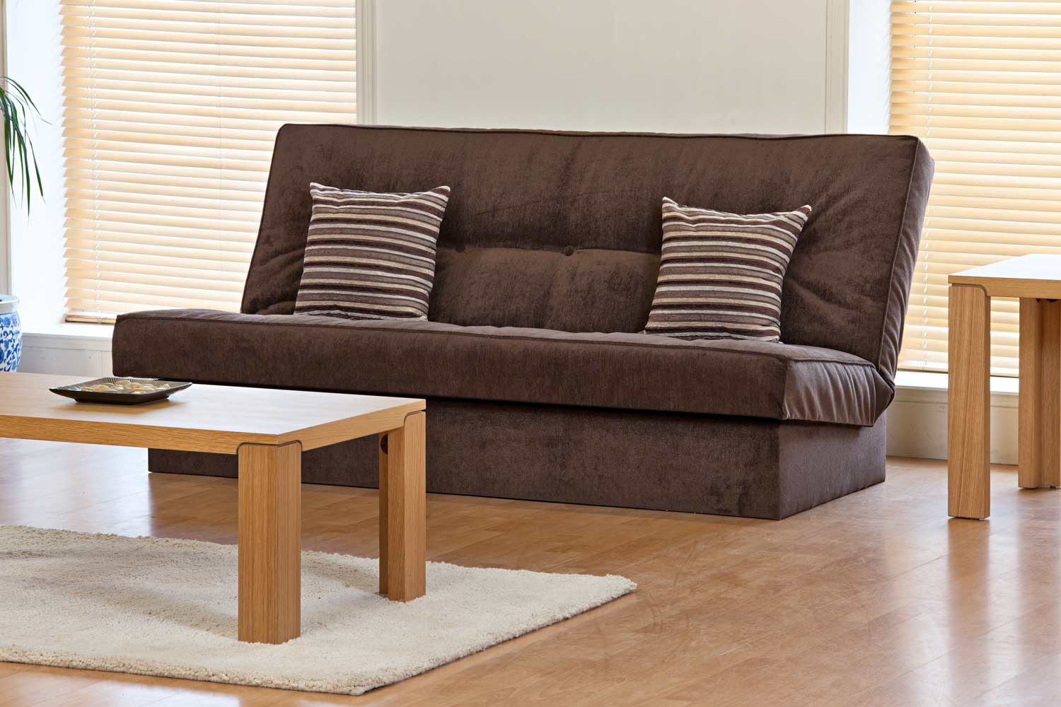 dark brown cheap futons with stripped cushions on wooden floor plus wooden  table and white carpet