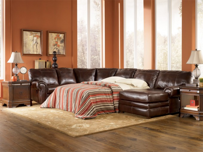 Dark Brown Leather Sectional Sleeper Sofa On Wooden Floor Plus Cream Carpet Matched With Orange Wall Plus Table Standing Lamp For Living Room Decor Ideas