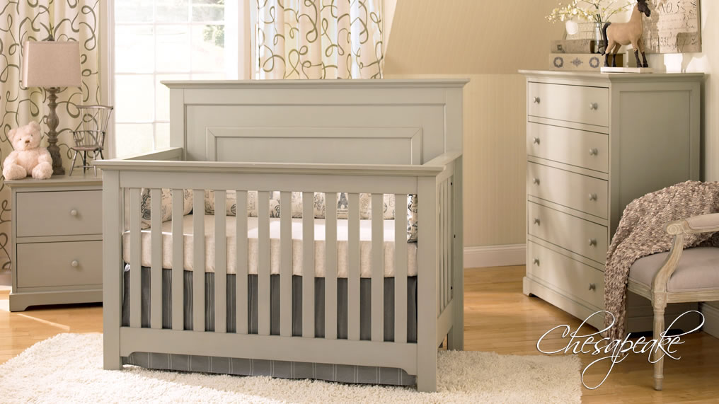 dark gray wooden munire crib on wooden floor plus white carpet plus matching dresser before the cream wall with white window with floral curtain for nursery decor ideas
