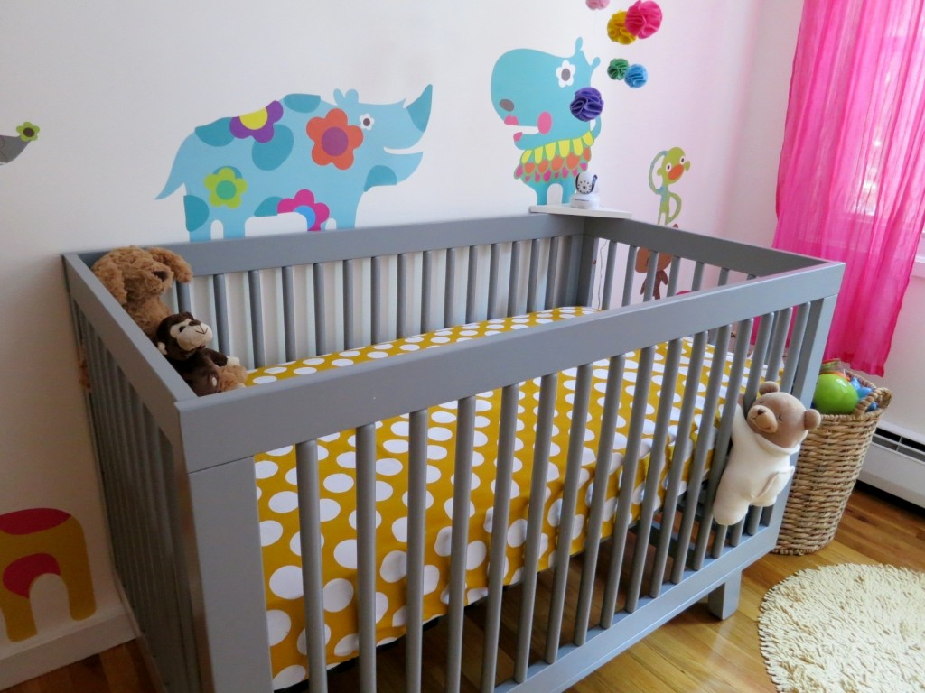 Grey Crib With Yellow And White Dotted Bedding By Babyletto On Wooden Floor Matched With White Wall With Animals Pictures Plus Dolls For Nursery Decor Ideas
