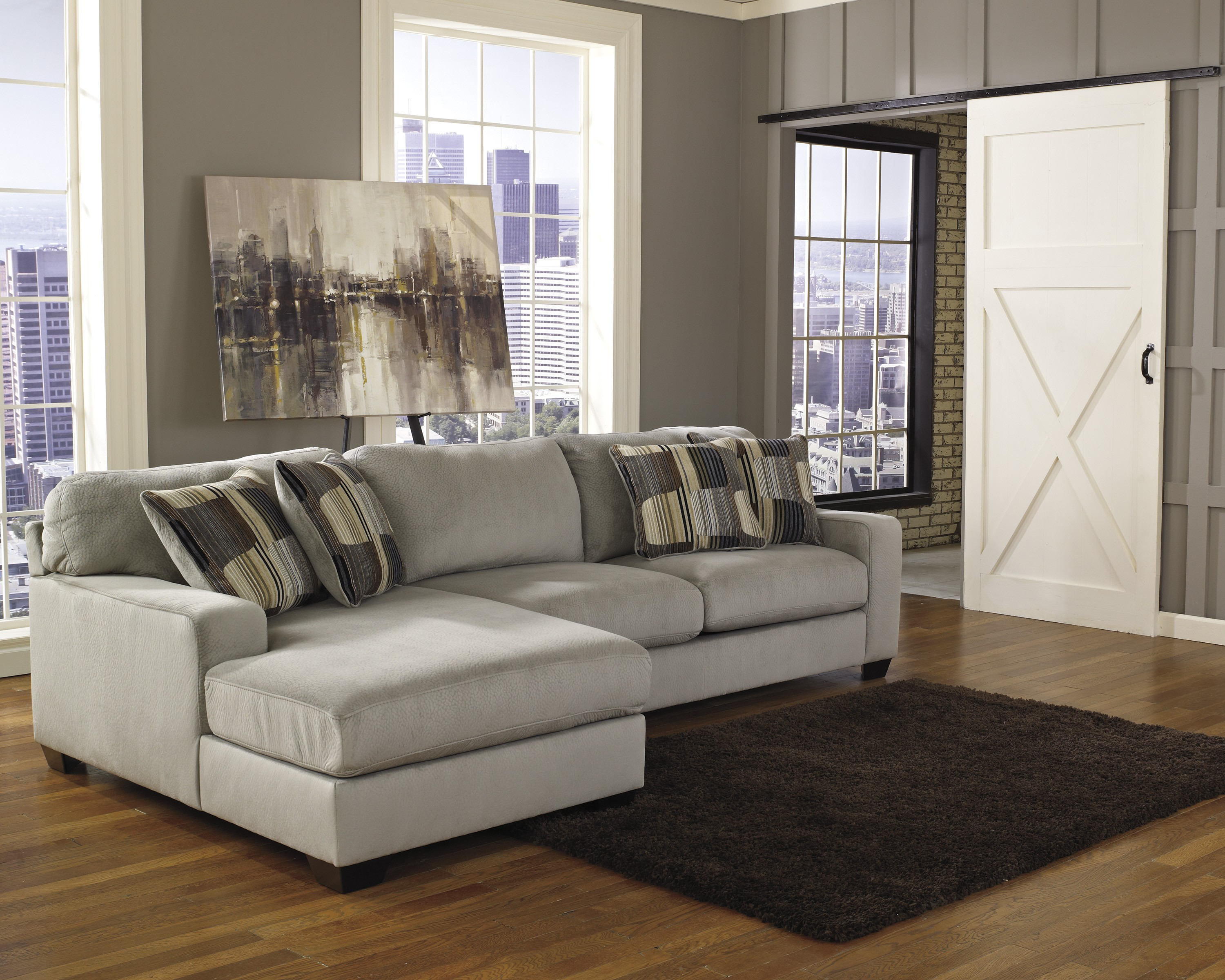 sectional in small living room. grey sectional sleeper sofa on wooden floor plus dark brown carpet matched  with wall Decorating Comfortable Sectional Sleeper Sofa For Living Room