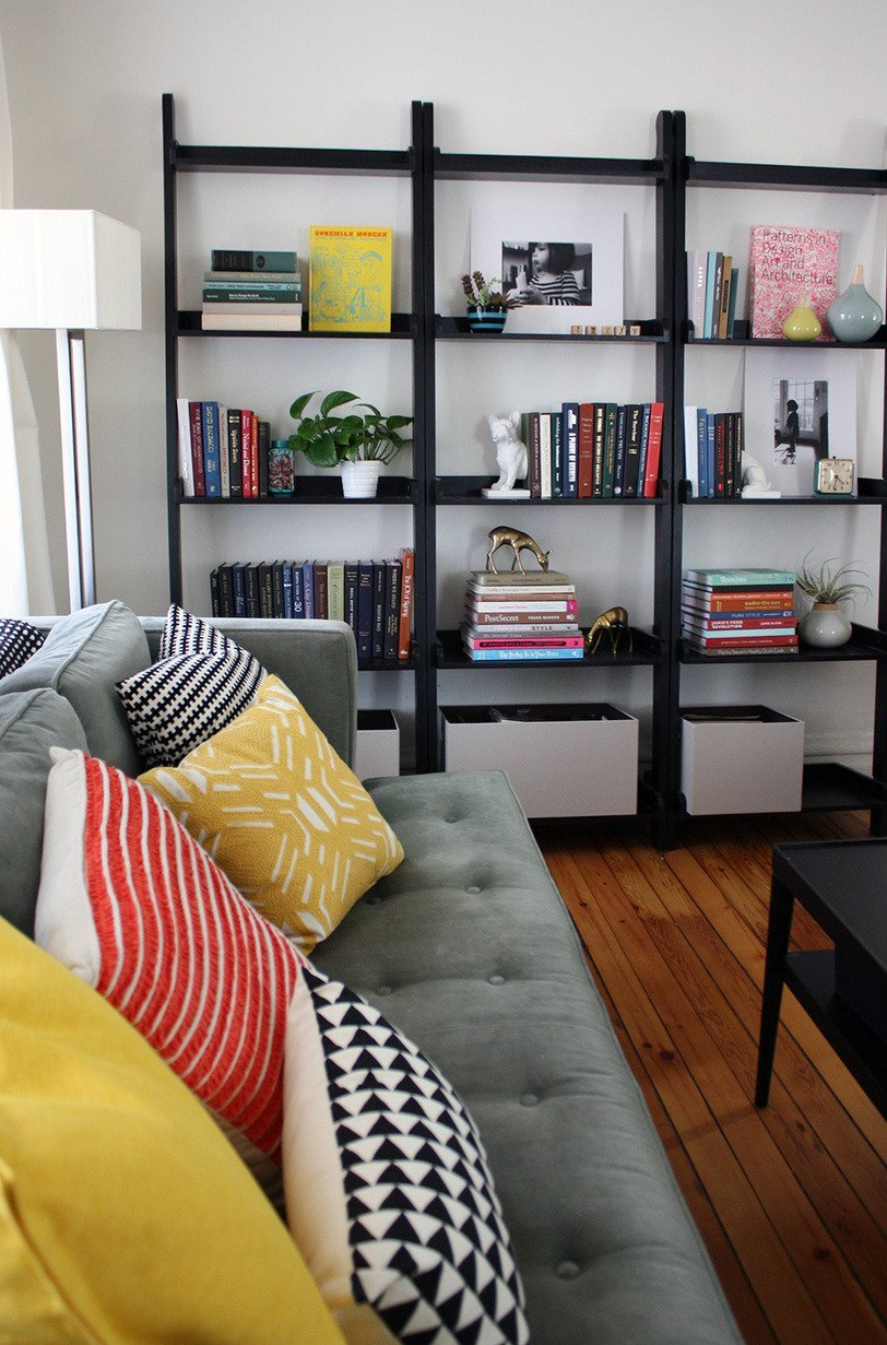 large ladder bookshelf in black on wooden floor matched with white wall plus sofa with cushion for smart living room decor ideas