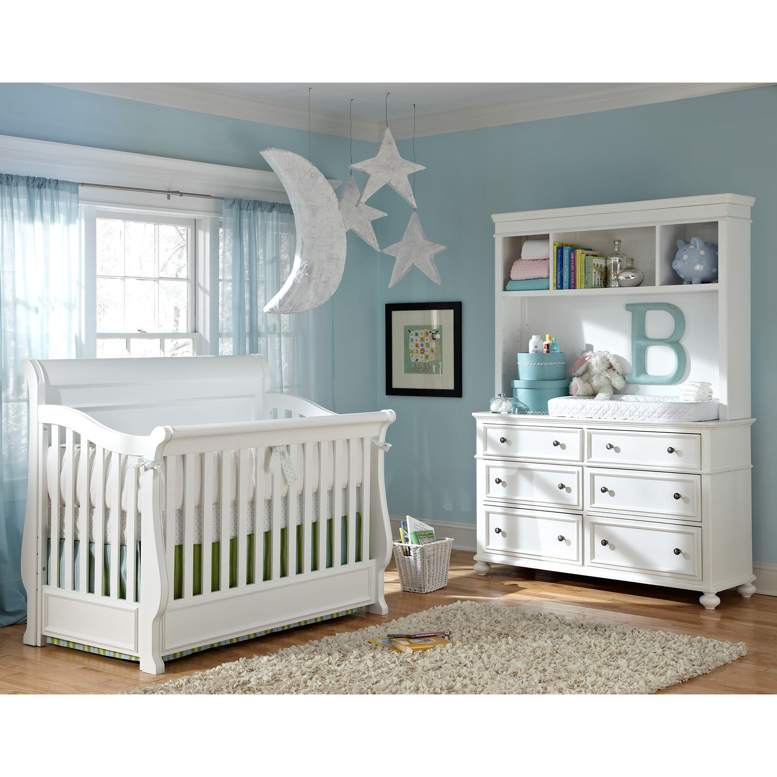 munire crib in white plus white armoire on wooden floor with wheat carpet matched with blue wall with white window plus curtain and hanging star and moon ornament for nursery decor ideas