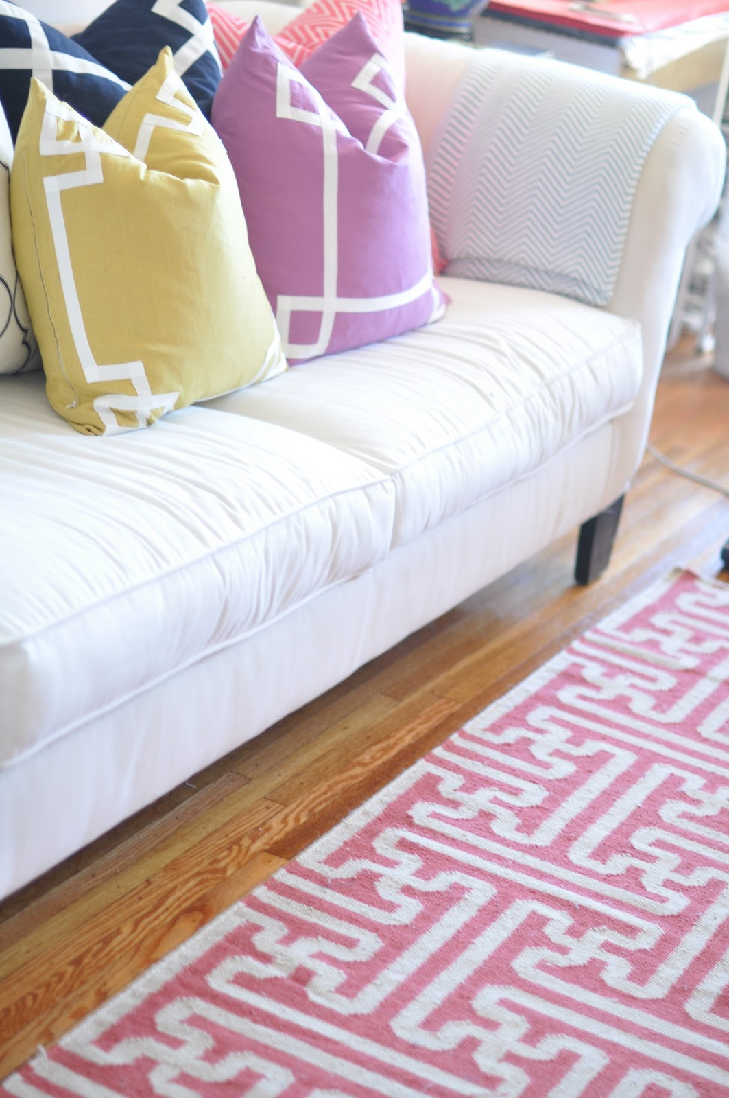 Pink And White Surya Rugs On Wooden Floor Plus White Sofa Plus Cushion For Inspiring Living Room Decor Ideas