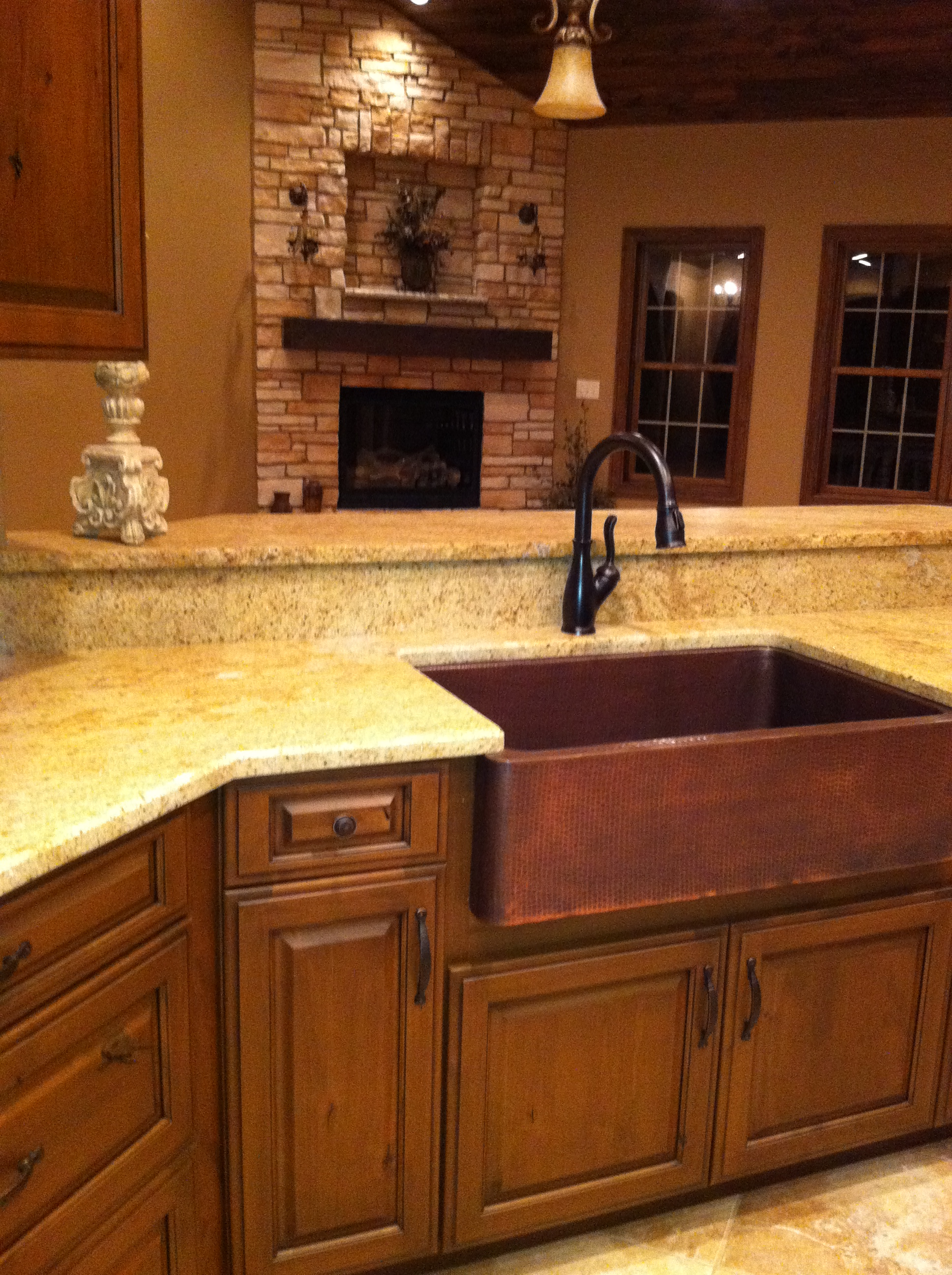 rectangle brown apron sink on brown wooden kitchen cabinet with black faucet on white marble countertop for kitchen decor ideas
