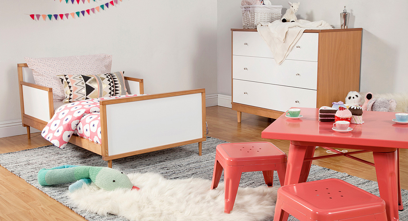 red desk by babyletto on grey carpet for nursery decor ideas
