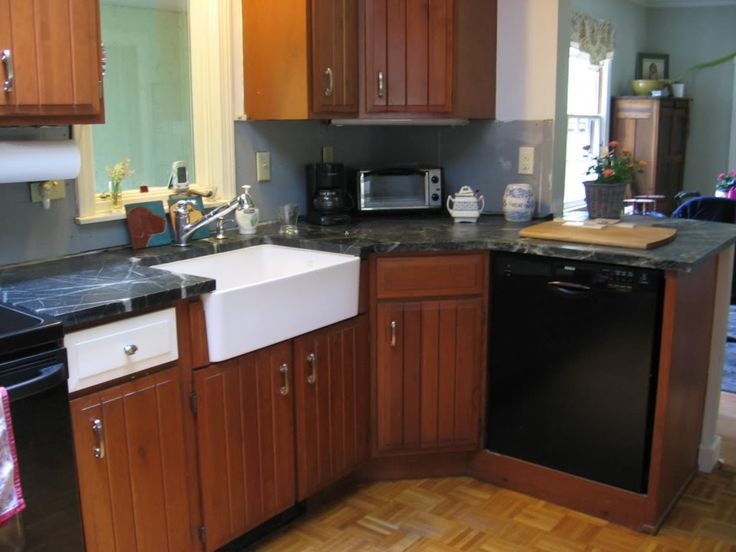 white apron sink on brown wooden kitchen cabinet with black countertop plus silver faucet plus stove on brown floor for kitchen decor ideas