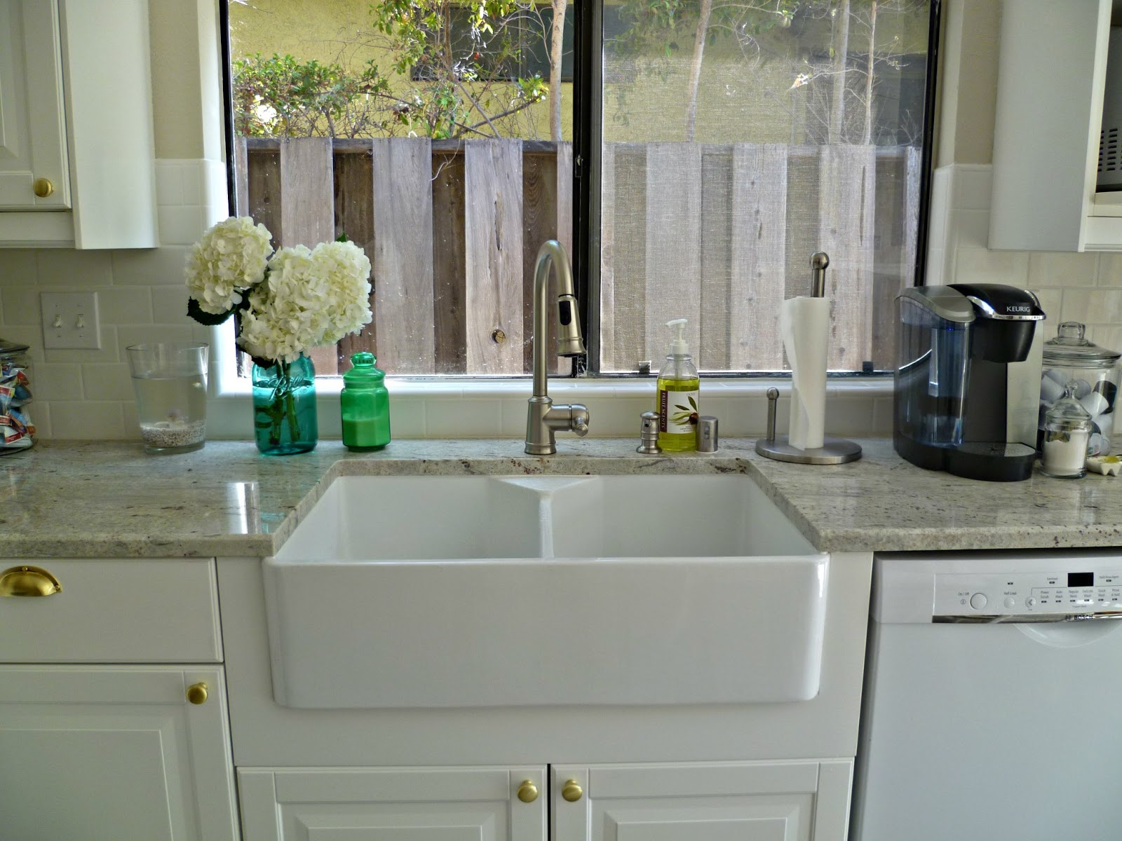 white apron sink plus faucet on white kitchen cabinet with wheat countertop before the glass window for kitchen decor ideas