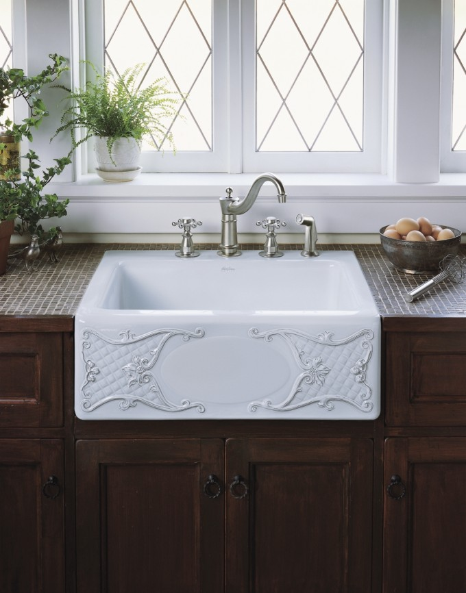 White Apron Sink With Charming Ornament Plus Faucet On Brown Wooden Kitchen Cabinets Before The White Window For Kitchen Decor Ideas