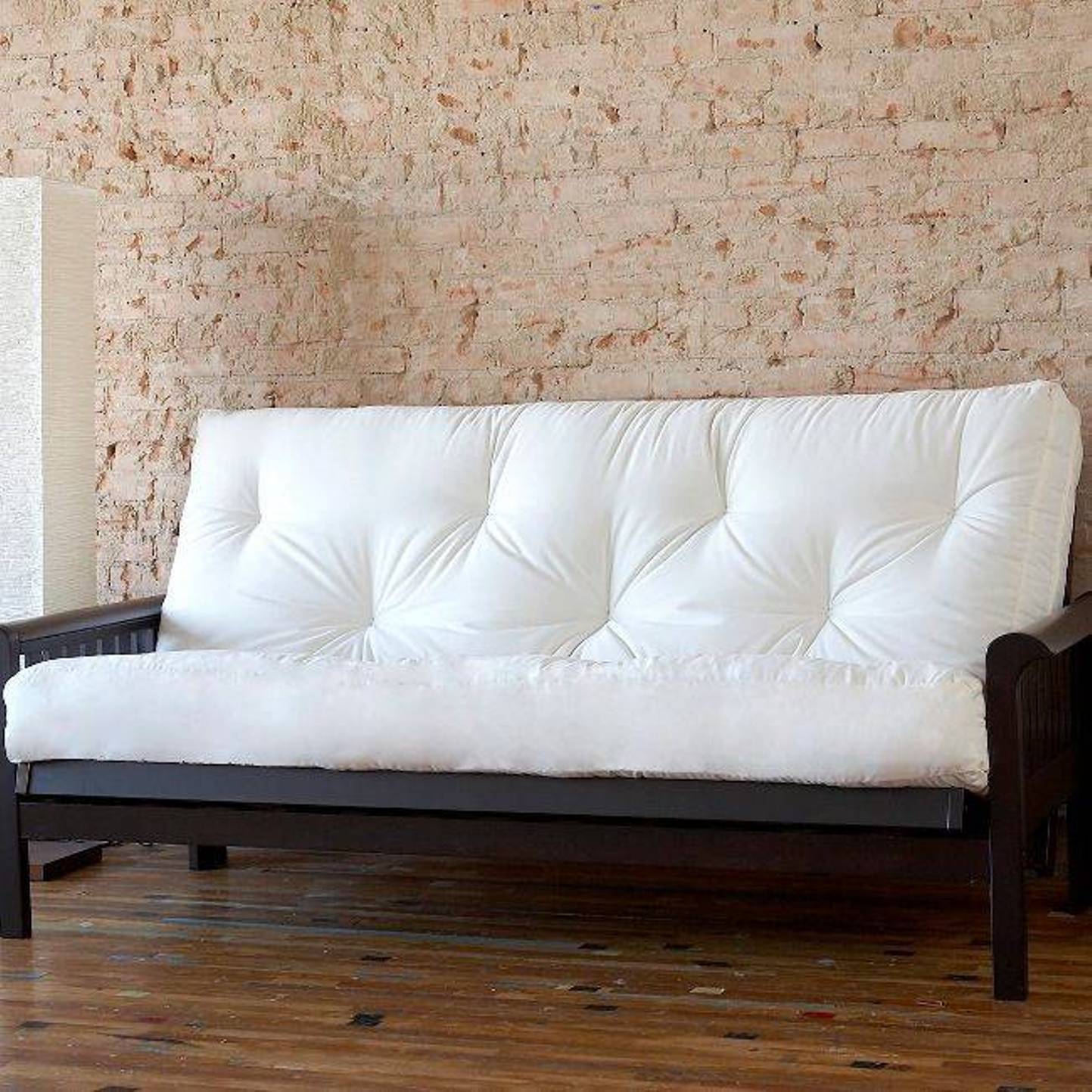 white cheap futons with black legs and arms on wooden floor matched with natural brick wall for home decor ideas