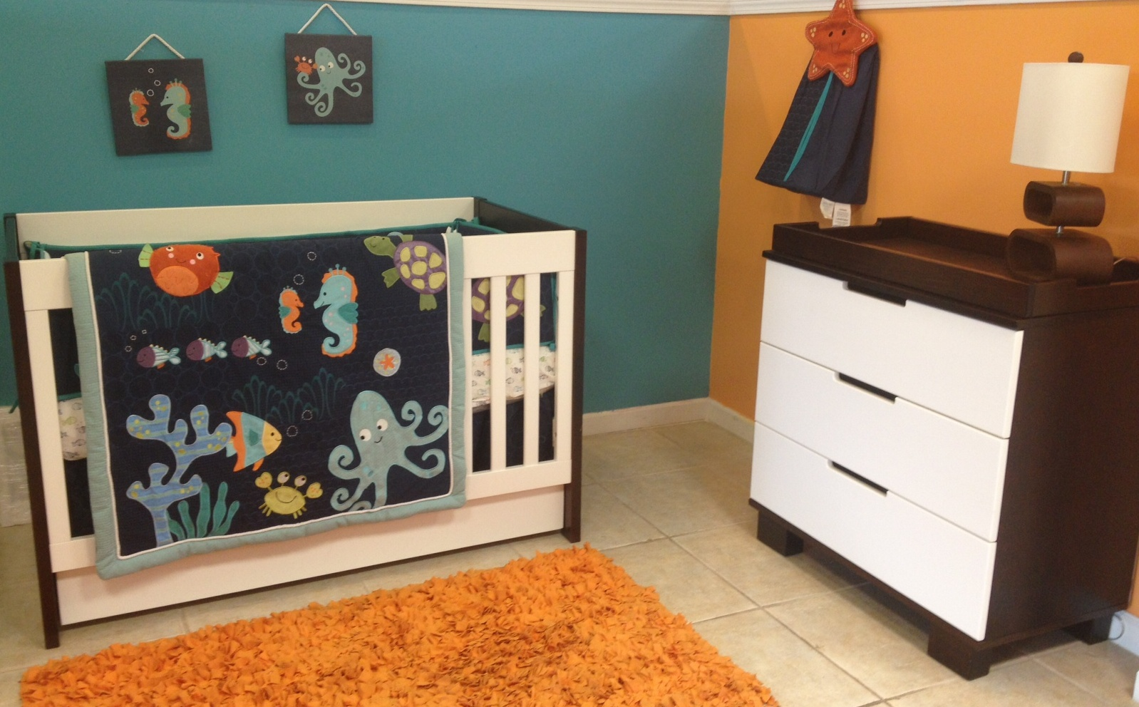 White Crib By Babyletto On Wheat Ceramics Floor Plus Orange Carpet Matched With Blue And Orange Wall Plus Wooden Cabinet For Nursery Decor Ideas
