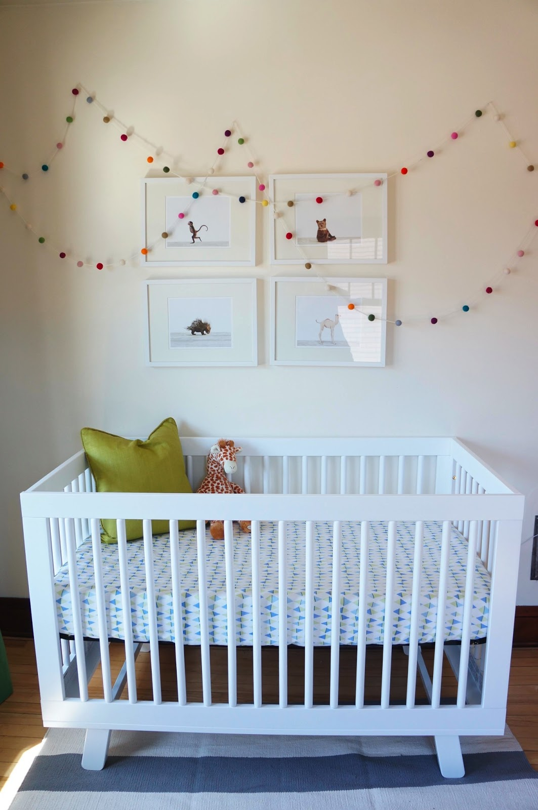 white crib by babyletto on wooden floor matched with white wall for nursery decor ideas