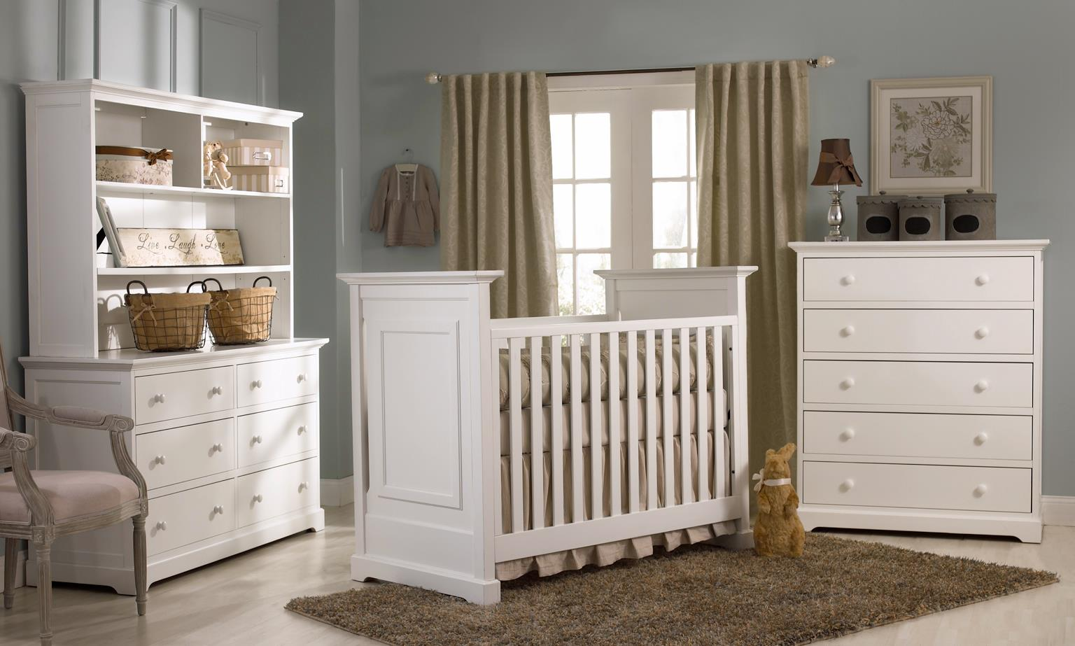 white munire crib on cream ceramics floor with tan carpet matched with blue wall with white window and tan curtain plus white dresser for nursery decor ideas