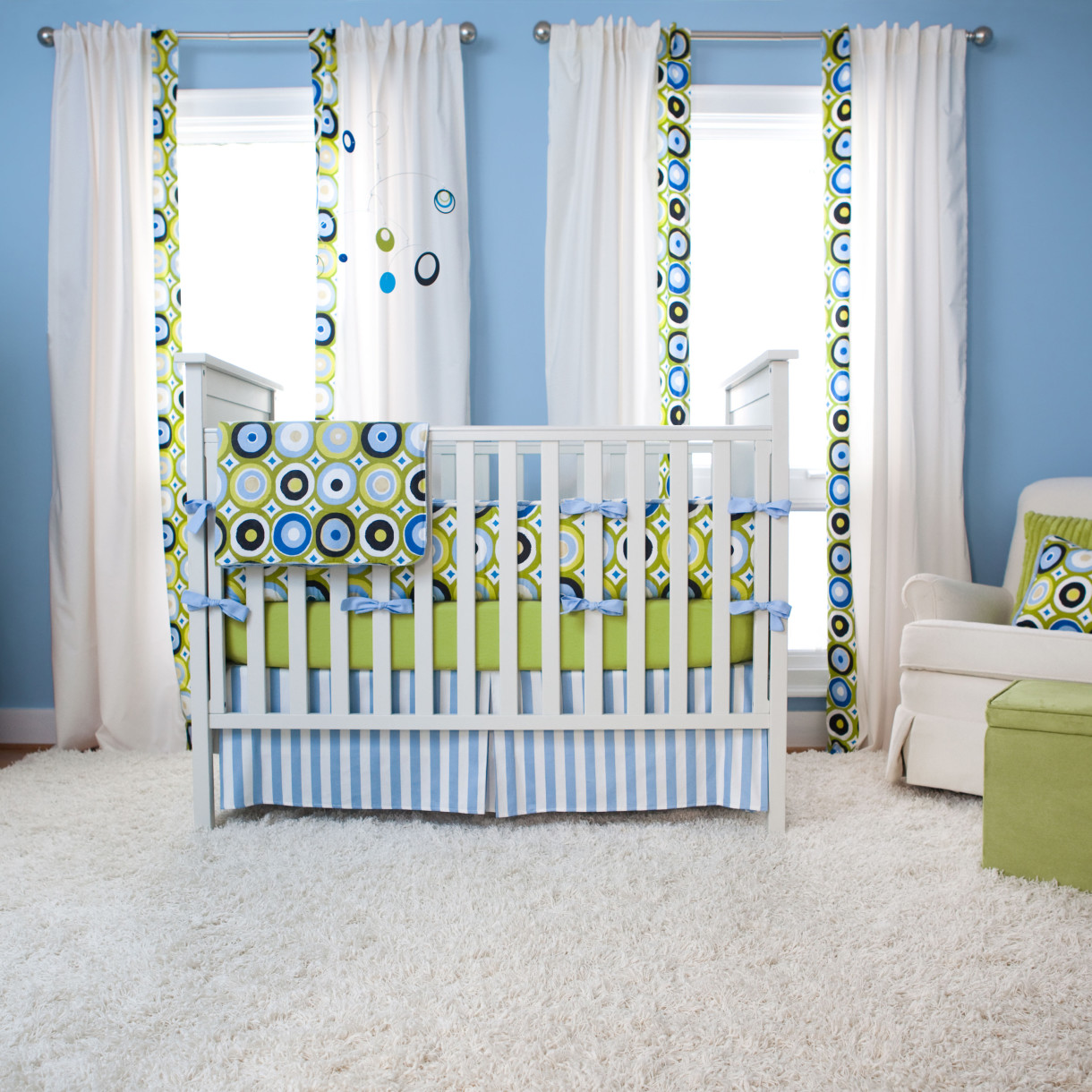 White Wooden Munire Crib With Colorful Mattress On Wooden Floor With White Carpet Matched With Blue Wall With White Window Plus Curtain For Nursery Decor Ideas