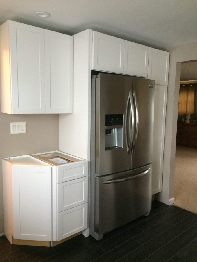 Awesome Kitchen American Woodmark Cabinets In White With Fridge On Black Wooden Floor For Kitchen Decor Ideas