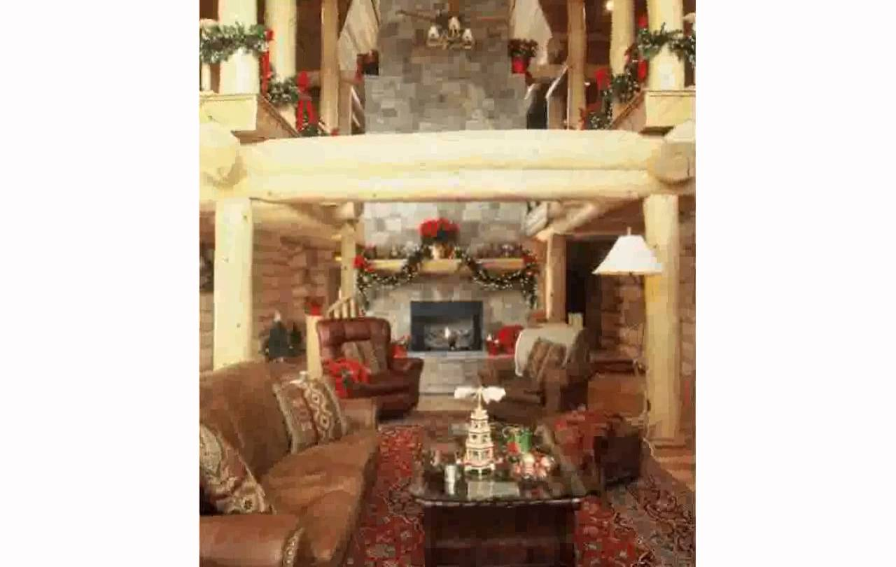 awesome living room design of Southland Log Homes with tan sofa set on floral rug plus fireplace ideas