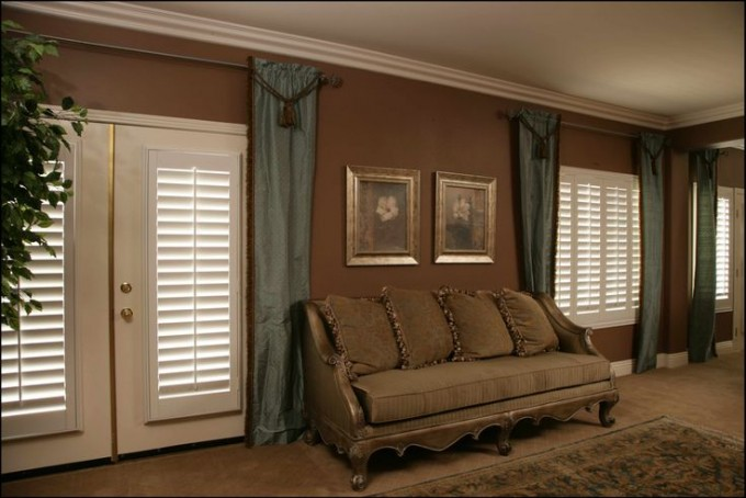 Awesome White Door And Sunburst Shutters On Brown Wall Matched With Wheat Floor With Floral Rug And Sofa For Living Room Decor Ideas