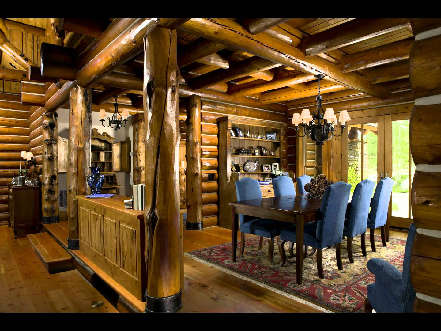 charming dining room decor of Southland Log Homes with dining table set on floral rug plus chandelier ideas