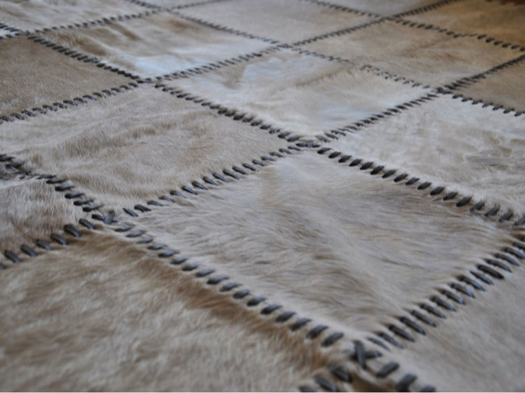 chic cowhide patchwork rug in creamy white with thin strip motif for floor decor ideas