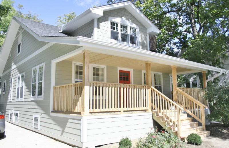 chic horizontal hardie plank siding in white with single hung window and wooden railing for home exterior design